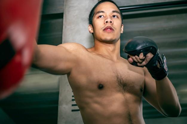 Sportowiec azjatycki mężczyzna bokser trening na worek treningowy na siłowni fitness.