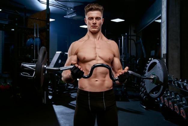 Sportowiec bez koszuli trenujący biceps ze sztangą.