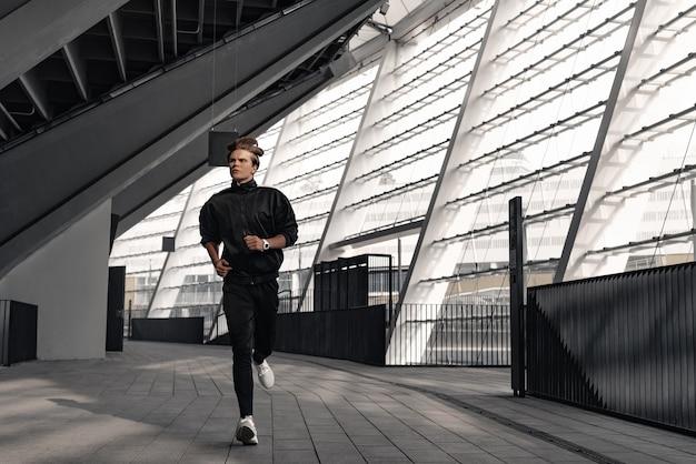 Sportowiec biegacz biegnie w pobliżu stadionu. człowiek jogging koncepcja odnowy biologicznej treningu.