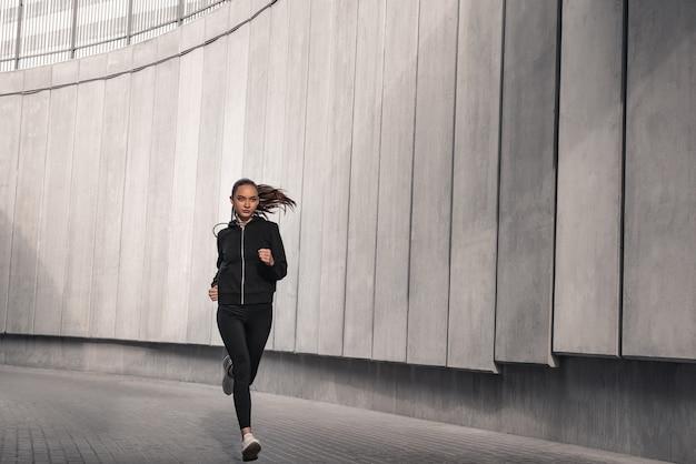 Sportowiec biegacz biegnie w pobliżu stadionu. kobieta jogging koncepcja odnowy biologicznej treningu.