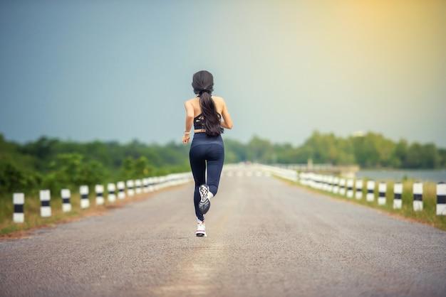 Sportowiec biegacz fitness słuchający muzyki w słuchawkach z aplikacji mobilnej na smartfony, która śledzi postępy. koncepcja odnowy biologicznej treningu.