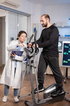 Sportowiec biegający na orbitreku, podczas gdy specjaliści medyczni nadzorują ćwiczenia, kontrolują aktywność fizyczną, mierzą tętno w laboratorium nauk o sporcie.