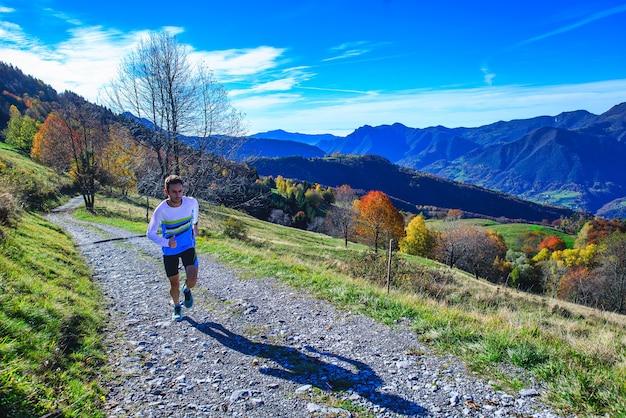 Sportowiec biegający w górach trenuje na polnej drodze