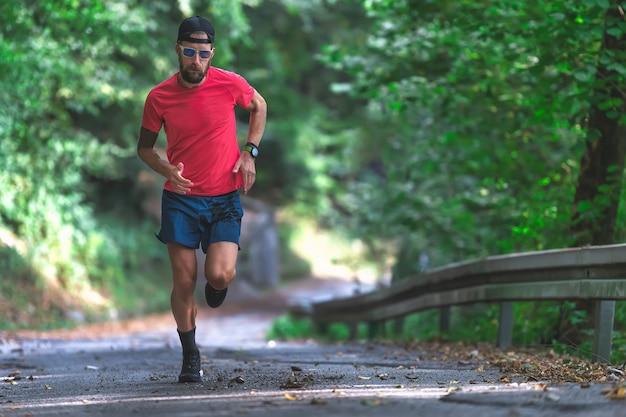 Sportowiec biegnący pod górę asfaltową drogą