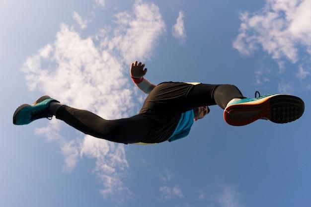 Sportowiec biegnie i skacze w niebo