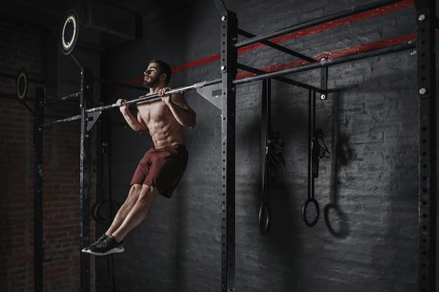 Sportowiec crossfitu podciągający się na siłowni.
