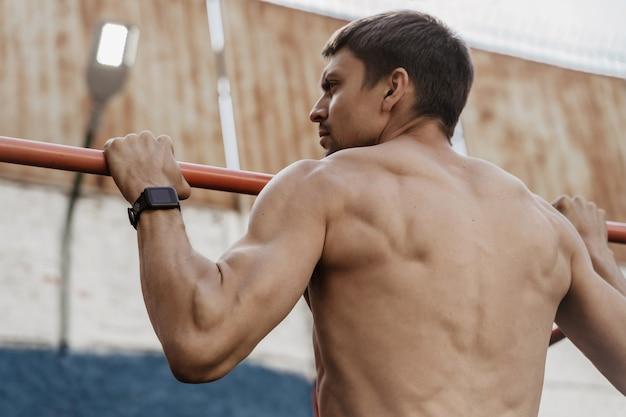 Sportowiec ćwiczący kalistenikę ze smartwatchem na nadgarstku