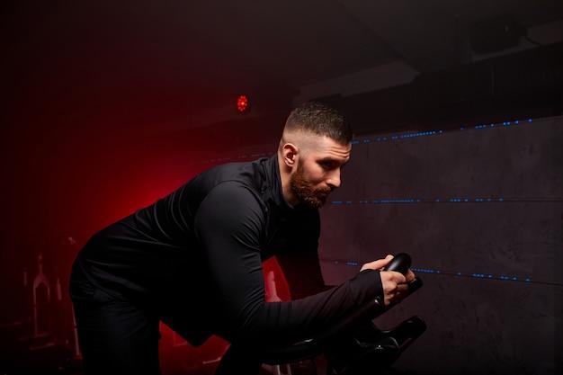 Sportowiec ćwiczy na zajęciach w siłowni, w zadymionej przestrzeni oświetlonej czerwonym neonem, w czarnym sportowym stroju, ma intensywny trening