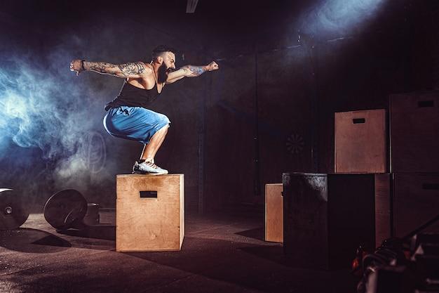 Sportowiec dał ćwiczenia. skacząc po pudełku. faza przyziemienia. zdjęcia z siłowni w ciemnym tonie. dym w siłowni.