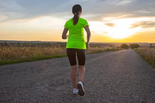 Sportowiec dziewczyna biegnie odległość na drodze przed niebo zachód słońca