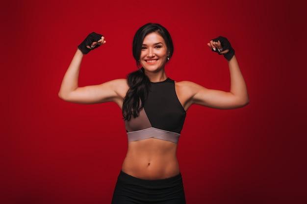 Sportowiec dziewczyna pokazuje bicepsy na czerwonym tle