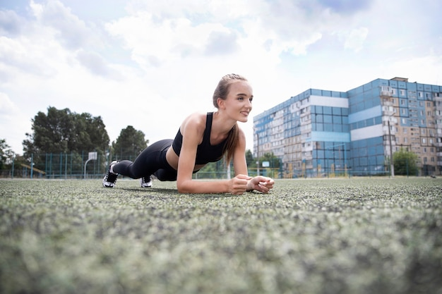 Sportowiec dziewczyna robi ćwiczenia na świeżym powietrzu. widok z dołu. aktywności sportowe. stojak sportowy, prasa, koncepcja fitness.