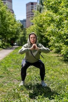 Sportowiec dziewczyna robi fitness w kraju w kucki z gumką fitness na nogach