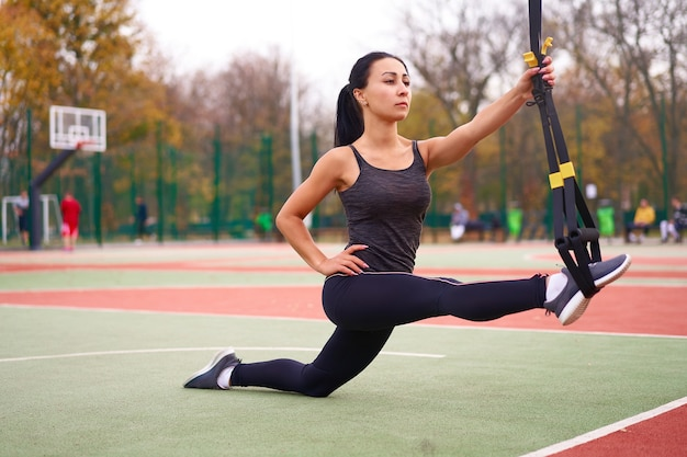 Sportowiec dziewczyna trenuje za pomocą trx na boisku. młoda, dorosła kobieta rasy mieszanej ćwiczy z systemem zawieszenia. zdrowy tryb życia. rozciągający plac zabaw na świeżym powietrzu.