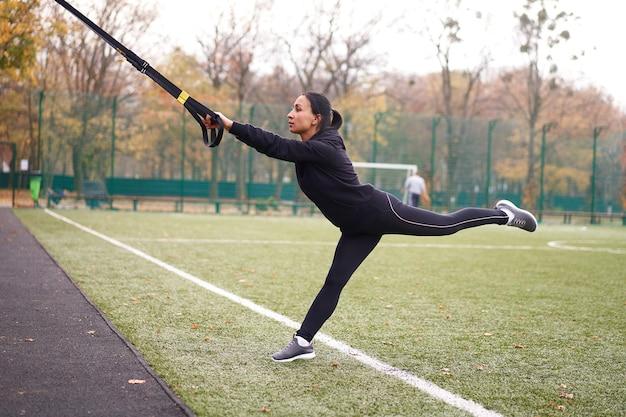 Sportowiec dziewczyna trenuje za pomocą trx na boisku