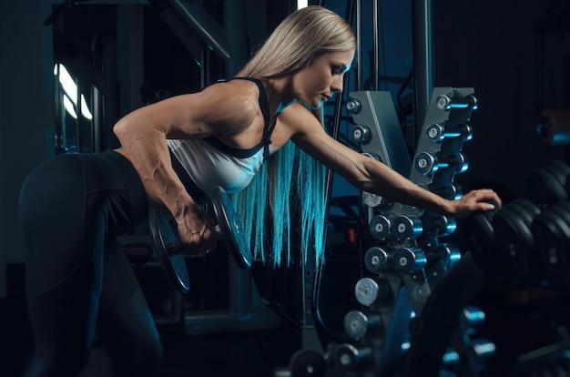 Sportowiec dziewczyna w stroju sportowym trenuje na siłowni