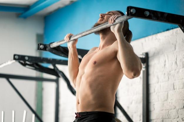 Sportowiec fitness model mężczyzna mięśni ciągnąc się na drążku w siłowni