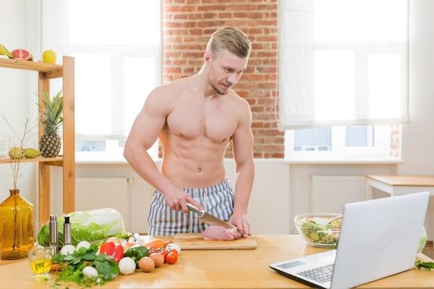 Sportowiec gotuje w kuchni, używa warzyw i różnych mięs do gotowania obiadów, ogląda kursy gotowania online