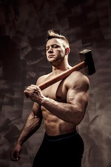 Sportowiec i młot. facet z niezłą kondycją mięśni, trener kulturysty trzyma duży metalowy młot