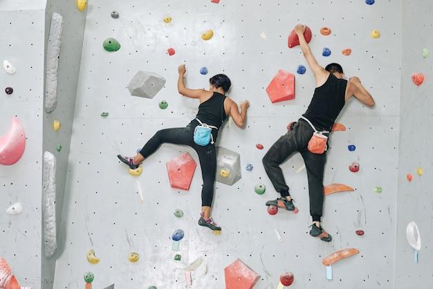 Sportowiec i sportowiec z workami z proszkiem magnezowym wspinający się po ścianie bulderowej, widok od tyłu