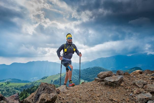 Sportowiec idzie na górę za panoramą gór