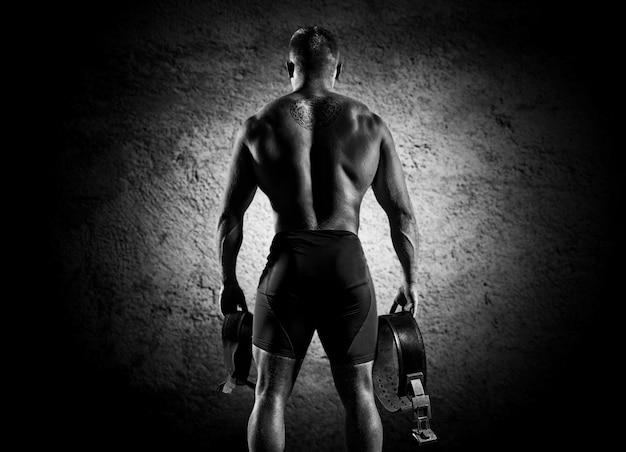 Sportowiec idzie na siłownię na trening. w rękach trzyma trampki i pasek. widok z tyłu
