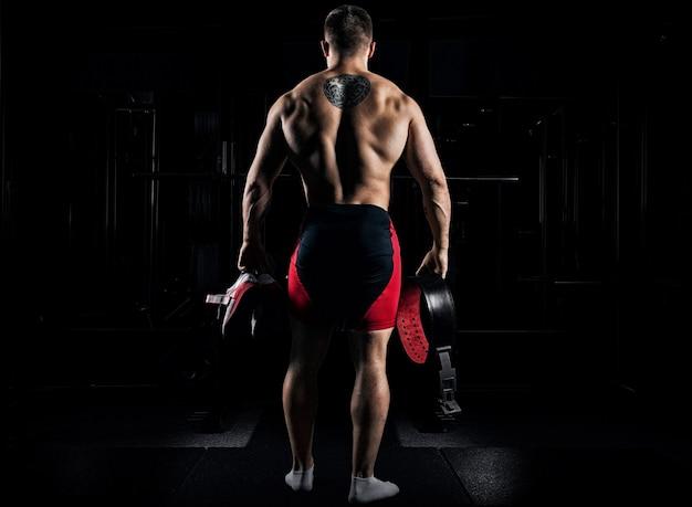 Sportowiec idzie na siłownię na trening. w rękach trzyma trampki i pasek