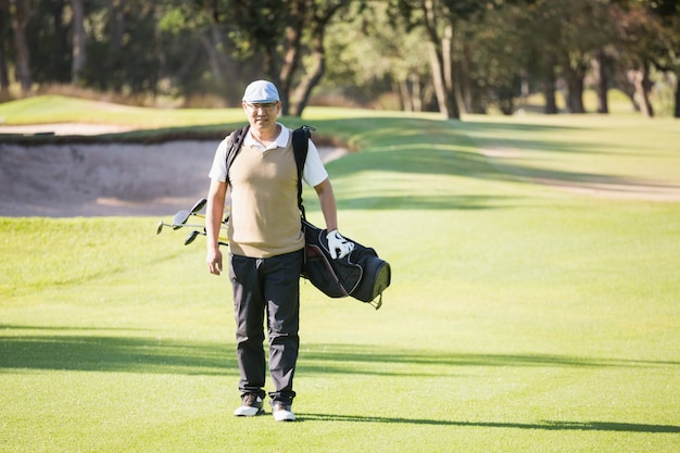 Sportowiec idzie ze swoją torbą golfową