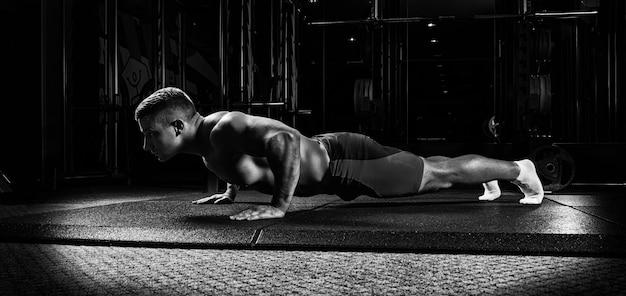 Sportowiec jest rozciągnięty na specjalnym pokrowcu na siłowni. widok z boku