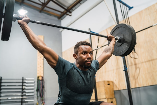 Sportowiec krzyś robi ćwiczenia ze sztangą.