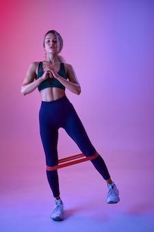 Sportowiec lekkoatletycznego robi ćwiczenia z gumą w studio, neonowe tło. fitness kobieta na sesji zdjęciowej, koncepcja sportu, motywacja do aktywnego stylu życia