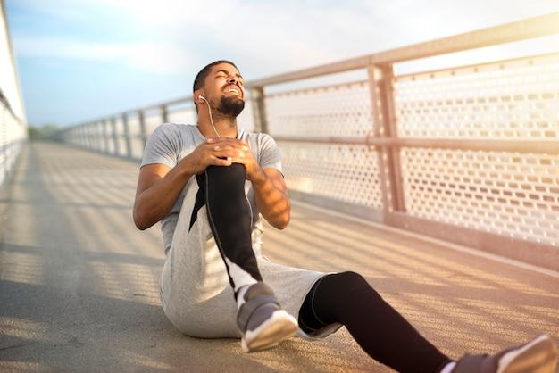 Sportowiec mający problem z kontuzją kolana podczas treningu biegowego
