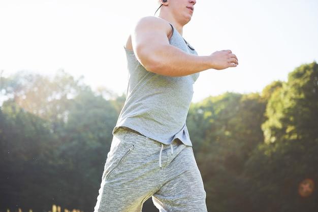 Sportowiec mężczyzna fitness jogging w przyrodzie podczas zachodu słońca.