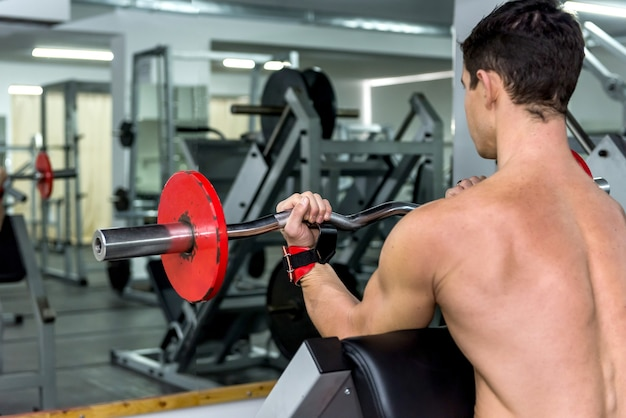 Sportowiec mężczyzna podnoszenia hantle w siłowni widok z tyłu