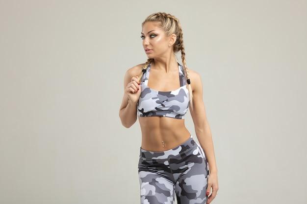 Sportowiec mięśni młoda kobieta na szaro.