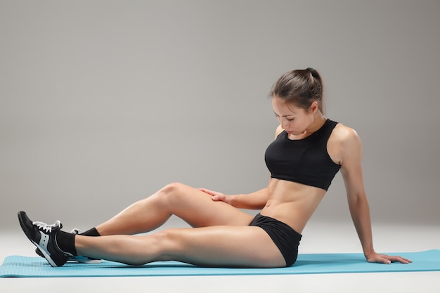 Sportowiec mięśni młoda kobieta, rozciągający się na szaro