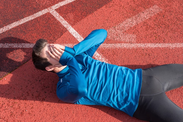 Sportowiec młody człowiek zmęczony, leżąc na bieżni.