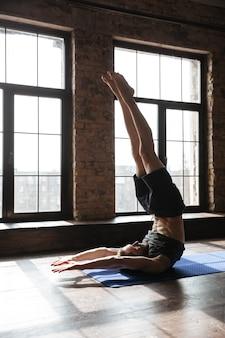 Sportowiec na siłowni wykonuje ćwiczenia jogi. patrząc na bok.