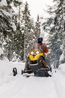 Sportowiec na skuterze śnieżnym w lesie zimą