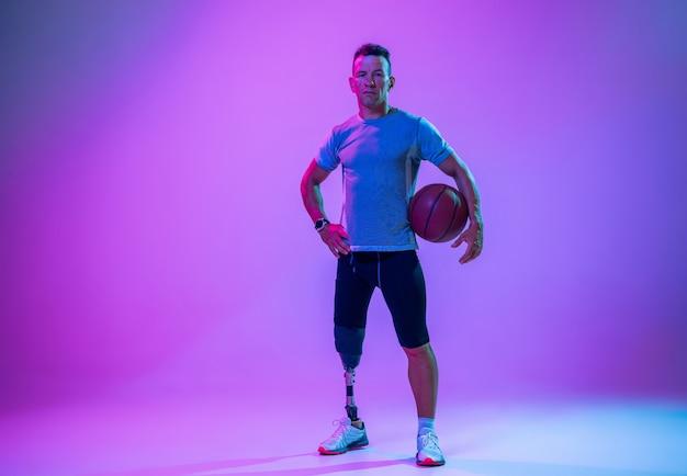 Sportowiec niepełnosprawny lub po amputacji na gradientowym tle studio w neon. gracz koszykówki