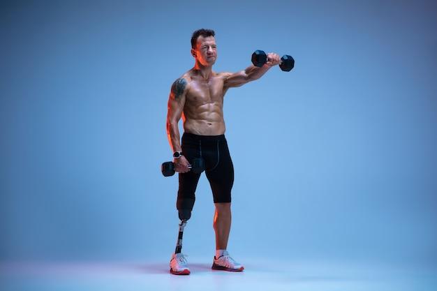 Sportowiec niepełnosprawny lub po amputacji odizolowany na niebieskiej ścianie profesjonalny męski sportowiec