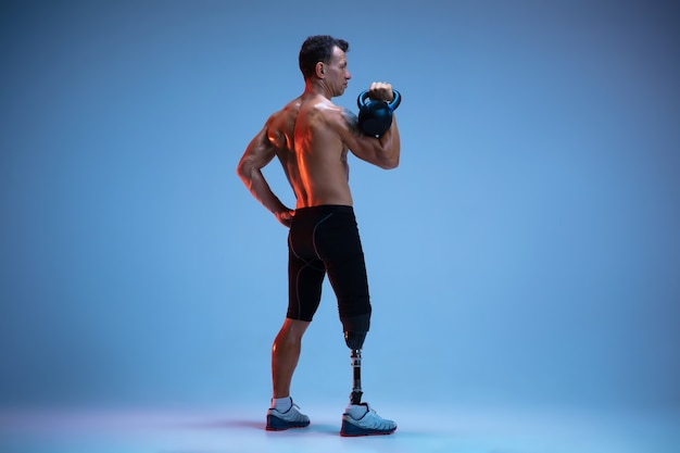 Sportowiec niepełnosprawny lub po amputacji odizolowany na niebieskiej ścianie
