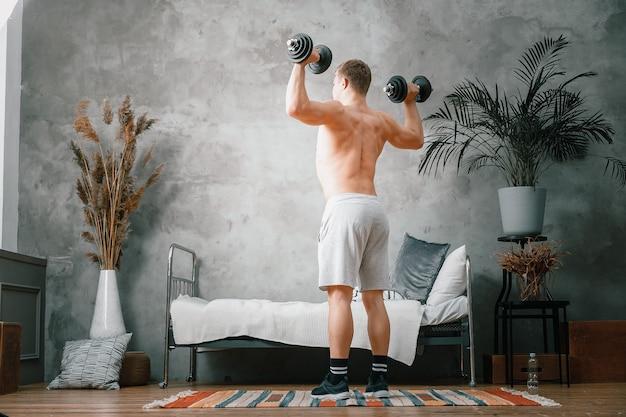 Sportowiec o blond włosach potrząsa bicepsami w hantlach w sypialni, trening online. młody człowiek uprawia sport w domu.