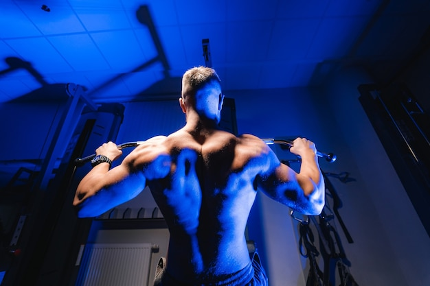 Sportowiec o silnym ciele wykonujący ćwiczenia wypychające na siłowni. widok z dołu. filtr światła niebieskiego.