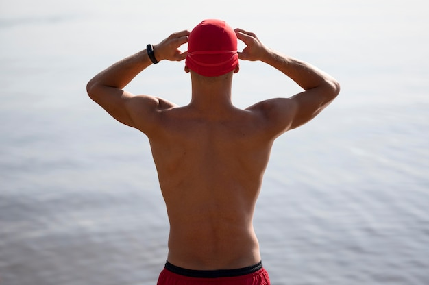 Sportowiec o średnim zasięgu, mocujący okulary pływackie