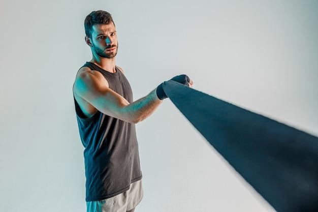 Sportowiec owijający bandaż bokserski na ramieniu. poważny młody bokser europejski nosi strój sportowy i patrząc na kamery. na białym tle na turkusowym tle. sesja studyjna