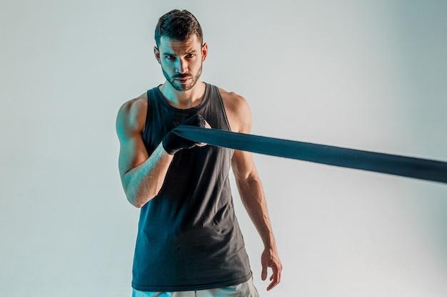 Sportowiec owijający bandaż bokserski na rękę. poważny młody bokser europejski nosi strój sportowy i patrząc na kamery. na białym tle na turkusowym tle. sesja studyjna