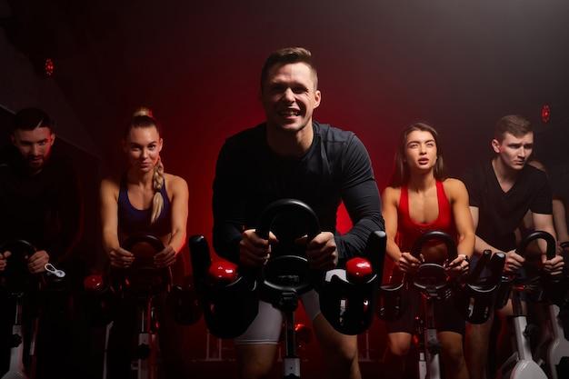 Sportowiec pilnie jedzie na rowerze stacjonarnym w siłowni, facet ćwiczy na rowerze stacjonarnym
