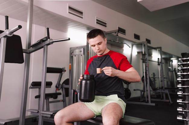 Sportowiec płci męskiej przygotowuje koktajl proteinowy lub używa suplementu diety dla sportowców na siłowni. żywienie sportowe