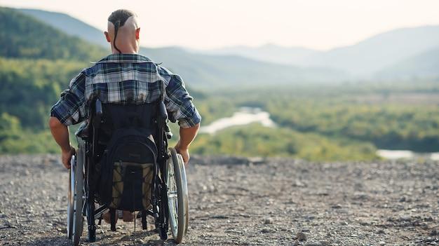 Sportowiec po kontuzji na wózku inwalidzkim cieszy się świeżym powietrzem w górach. rehabilitacja osób niepełnosprawnych.